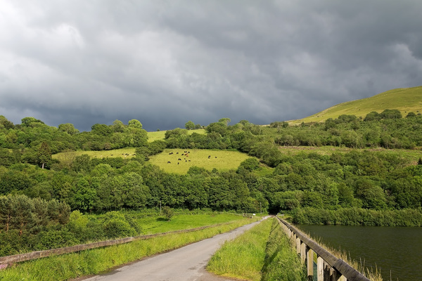 Rural road with storm: A rural road with an approaching storm in eastern Wales.