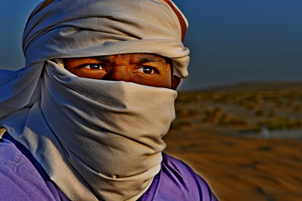 Desert man with Head Scarf: Portrait of Arab man in the desert of Saudi Arabia, Skin dark and red from the heat and sand all around him .  Photo image for wall art, artwork or local art . Burka is covering his head except his eyes .