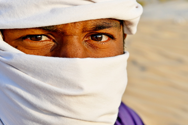 Arabic Indian Man in desert: Arabic Indian man in desert with head scarf a traditional culture that is going on for hundreds and hundreds of years in the Arabic countries and in Saudi Arabia . Photos in desert on the desert hill with sand only in the area and everywhere in the backgr