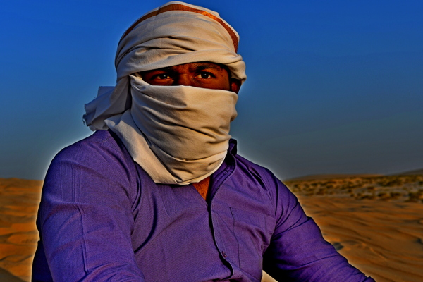 Indian man in the desert sand: Arabic Indian man in desert with head scarf a traditional culture that is going on for hundreds and hundreds of years in the Arabic countries and in Saudi Arabia . Photos in desert on the desert hill with sand only in the area and everywhere in the backgr