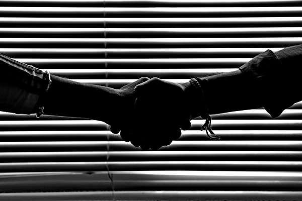 Handshake  in Monochrome: Handshake of two men hands on a window with striped pattern of light and shadows, the silhouette is very dark and the image is very dark and the black and white is more emphasized