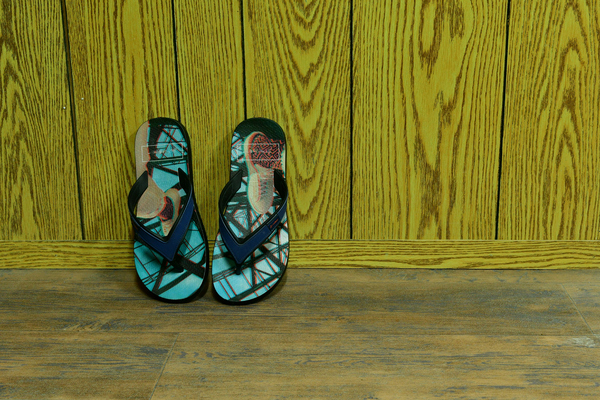 Flip-Flops on the wall: Sandals & Flip-Flops on the wall in the corner of the floor and wall inside the house., the floor is wooden and the wall also made of wood panels and the sandals are in beautiful colours