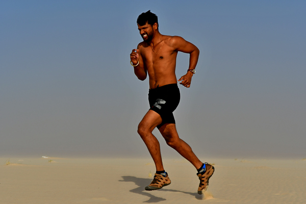Young adult running the sun: Young adult man, is running on the sand hill in desert area and he is enjoying the sand and sunlight. His slim body suggests that he is a fitness model working out daily to maintain a healthy life style and healthy living habits. Fitness exercise and card