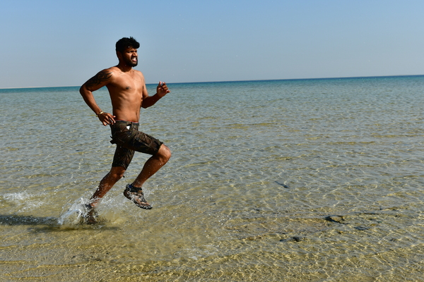 Running man in the water: A runner at the beach running and splashing water . Run in the water is more difficult and it makes more muscle than jogging or any other work out. Fitness and good lifestyle, eating habits and healthy living are very important for long life.