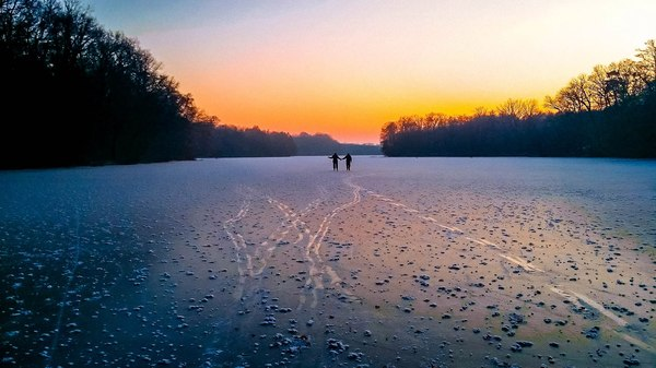 Ice rink on forest lake: Two people in winter on a frozen forest lake