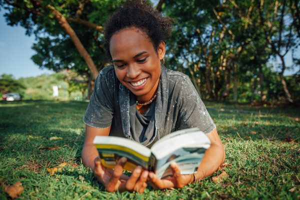 Summer day in the park: Beautiful young woman with afro hairstyle and book in her hands lying on the grass in the park on sunny summer day