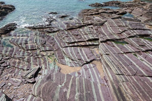 Striped rocks: Strange purple and grey striped sedimentary rocks on the coast of Daymer Bay, northern Cornwall, England.