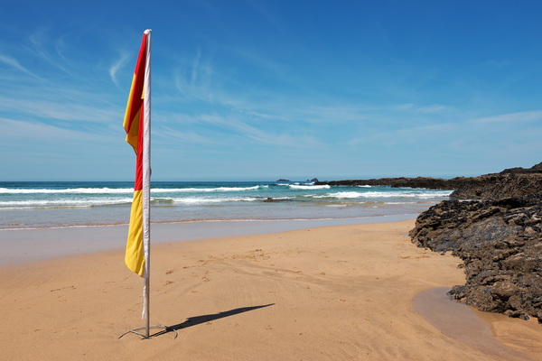 Beach safety flag: A flag indicating where to swim, and that a lifeguard is on duty, on a beach in northern Cornwall, England.