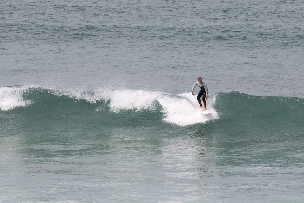 Surfer: Surfboarding in Cornwall, England.