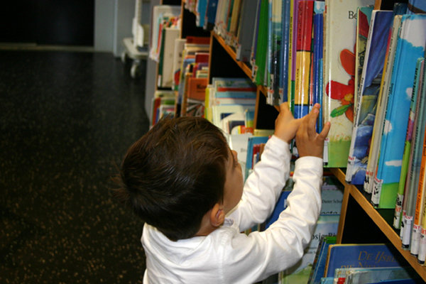 at the library: a little boy picking a book at the library