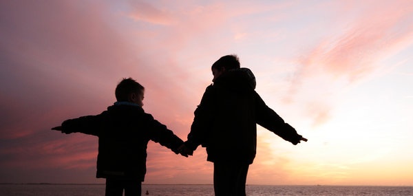 children: two kids against the sunset sky