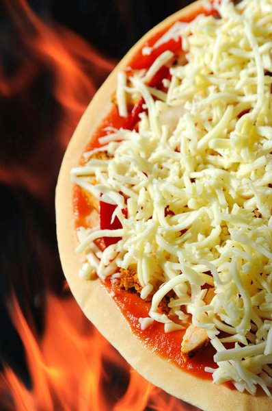 Pizza Prepared: A pizza topped with cheese on a flamed background ready to be cooked