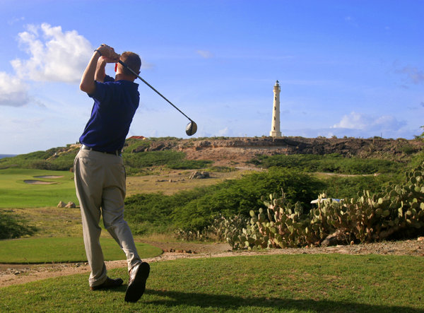 Aruba Golf: Golfer tees off on an Aruba Golf Course. Lighthouse in background