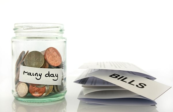 Rainy Day Savings: Clear glass jam jar with coins inside savings concept