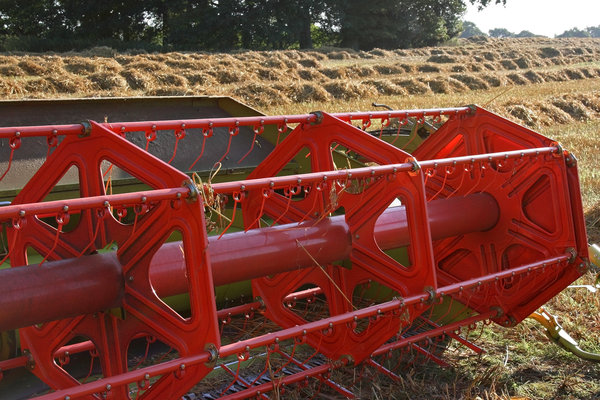 Harvester: The threshing wheel of a combine harvester in a field in West Sussex, England.