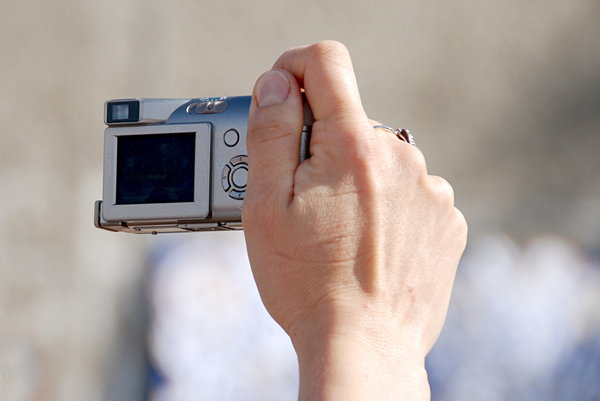 Compact photo camera in action: Woman's hand with little camera