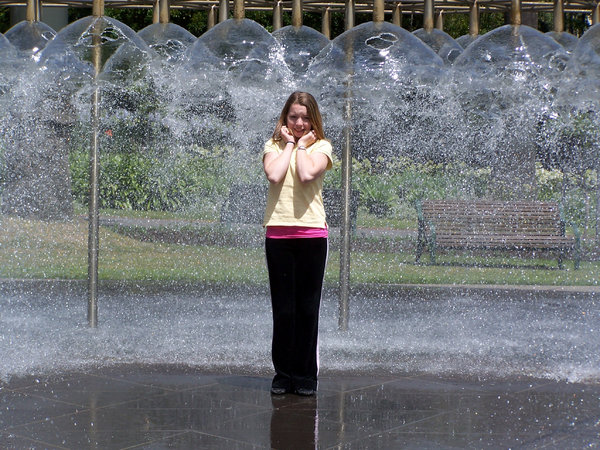 Oh no, I dont want to get wet!: girl trying to avoid the water of the fountain as it went on.