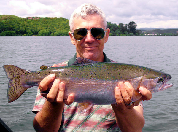 Proud fisherman: trout caught by proud fisherman, Lake Rotorua, New Zealand.  Don't think I'm experienced enough to clone out that corner successfully.  Have straightened and cropped somewhat... crop more?  Thankfully it was fairly calm on the water, boat not too rocky.