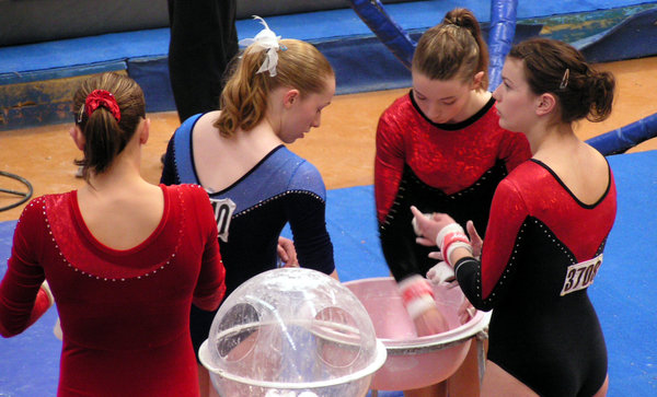 Chalking the hands: Gymnasts chalking their hands before competing bar.