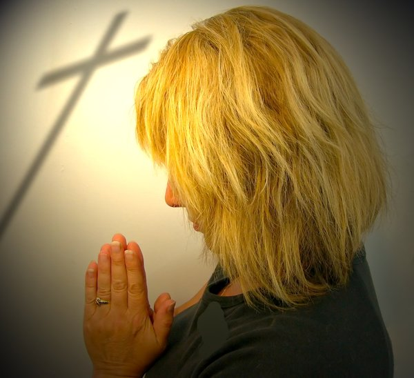 Easter Prayer: A woman praying, with the shadow of a cross in the background. Special light.