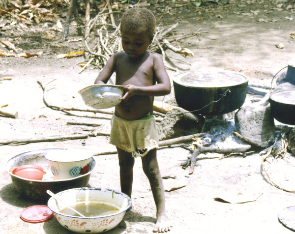 child making breakfast: A child making breafast in a small rural village near Bo, Sierra Leone
