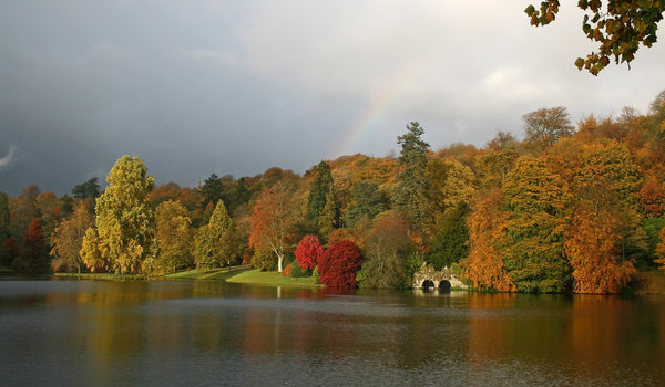 Lakeside with rainbow: Lakeside woodland in southwest England in autumn, with the end of a rainbow.