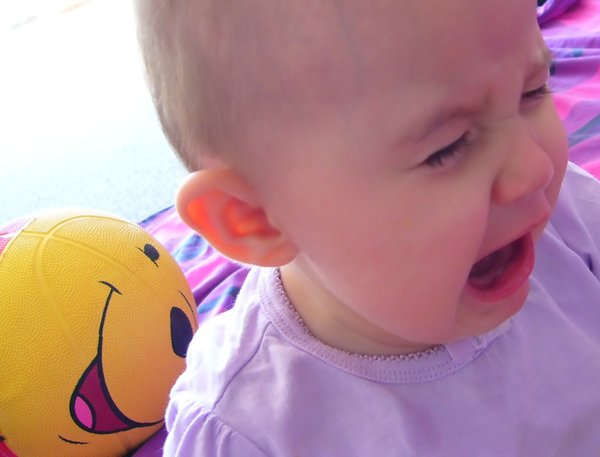 Baby Crying: A baby crying, contrasted with a happy face on a toy in the background. I wish the child was clearer, but I hope it's useful.