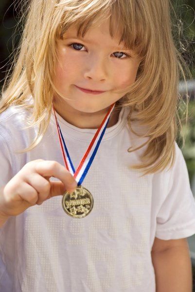 Child and medal: Little girl proudly showing her gold medal