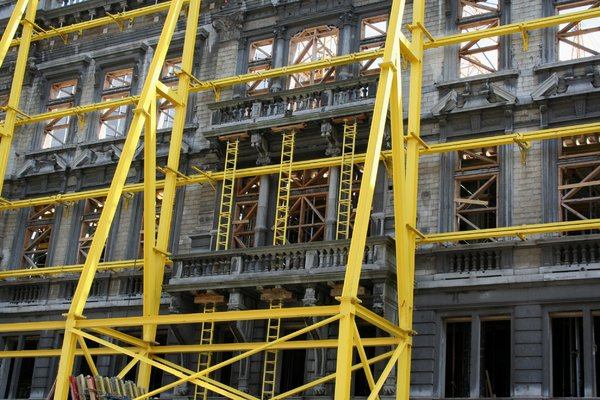 yellow scaffold: A yellow scaffold in front of an old house during renovation