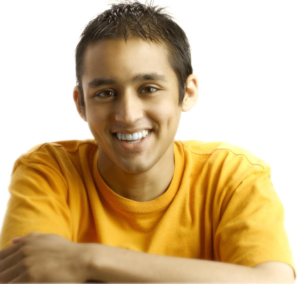 Smiling portrait: portrait of a boy in orange tshirt on a clean white background with good lightingPerson in the Photograph: Nikhil Bhat