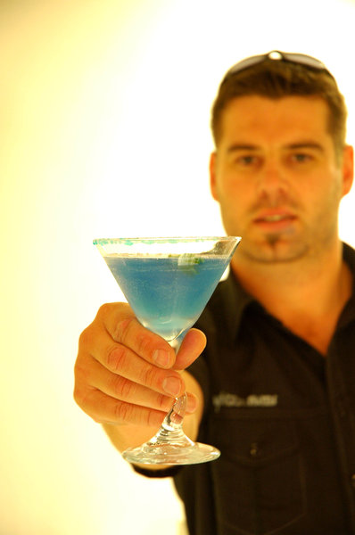 Barman offering: Barman offering a cocktail.NB: Credit to read