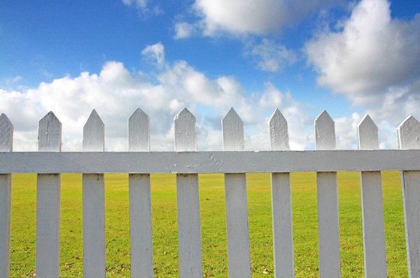 Picket Fence: A white wooden picket fence against a blue sky