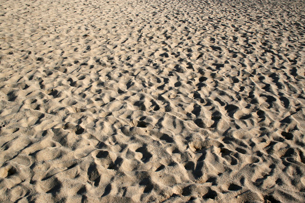 Footprints: Footprints on a busy sandy beach in Sardinia.