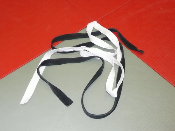 Judo: Judo belts on a tatami symbolizing the begin of a Judo career with the white belt and its masterchip with the black belt
