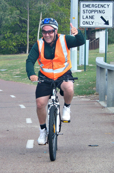 cheery cyclist: cyclist on public cycleway giving thumbs up greeting