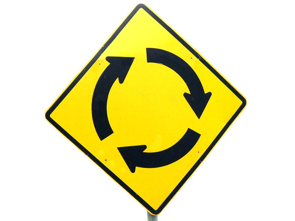 in circles: black on yellow street sign indication a roundabout