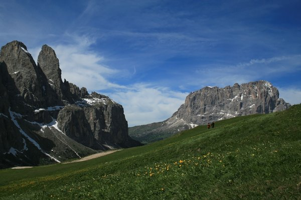 Mountain stroll 1: Walkers enjoying a flower meadow high in the Dolomites, Italy.