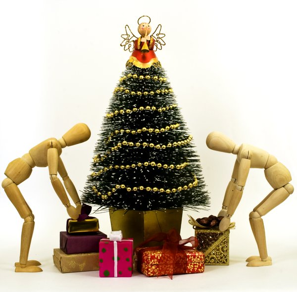 Finishing Touches: Decorated minature Chrismas tree with presents.  Wooden mannequins adding finishing touches.