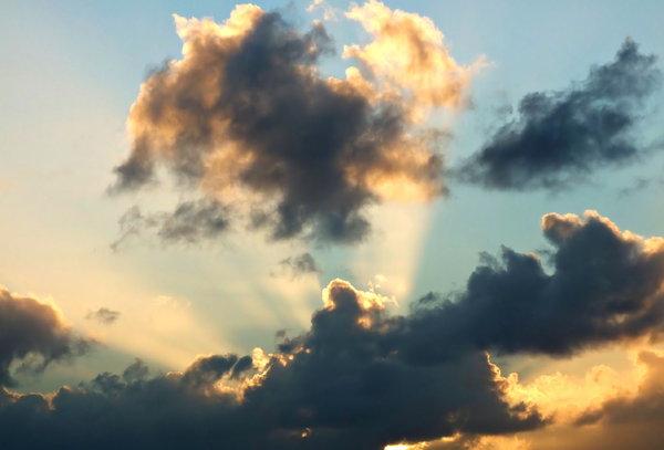 heavenly light: golden sun rays spreading from behind dark storm clouds