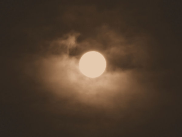 sepia moon: moon halo on cloudy misty evening in old sepia colour
