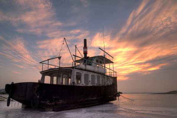 Old ferry in sunset - HDR: An old ferry locked in ice. The picture is HDR.