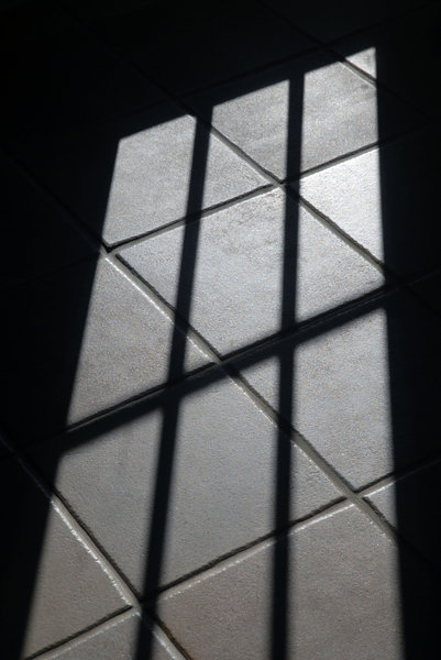 Window Shadow: Shadow on a tile floor made by light through a window.