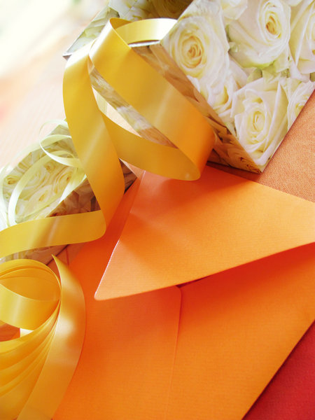 wrapping a gift: a box with roses, an envelope and some ribbons in warm colours.