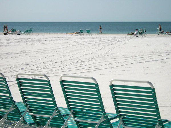 Beach Chairs: People play in the sand and surf on a white sandy beach on Siesta Key Florida