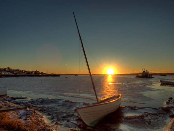 Boat on icy water - HDR: Sailing boat at the shore of a frozen fjord. The picture is HDR.