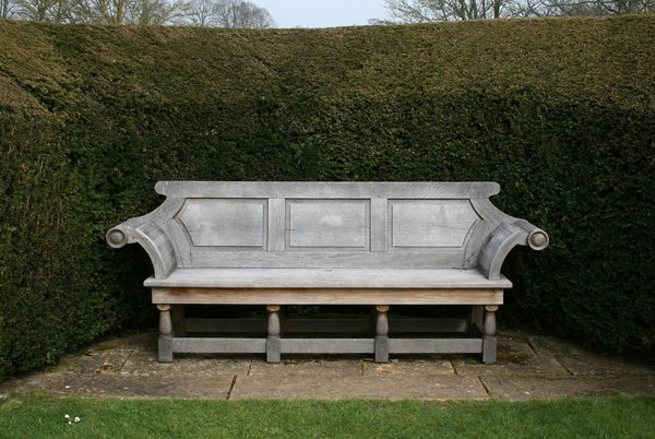 Ornate garden bench: An ornate wooden bench in a garden in Somerset, England.