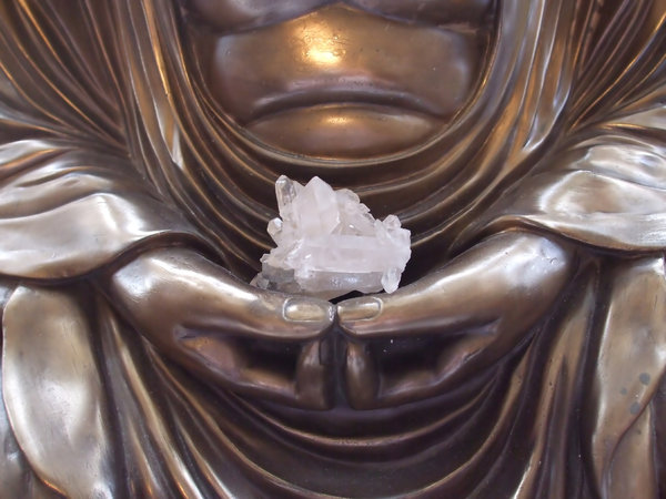 Buddha Holding Crystal: Shot of a crystal in the hands of meditating Buddha statue.