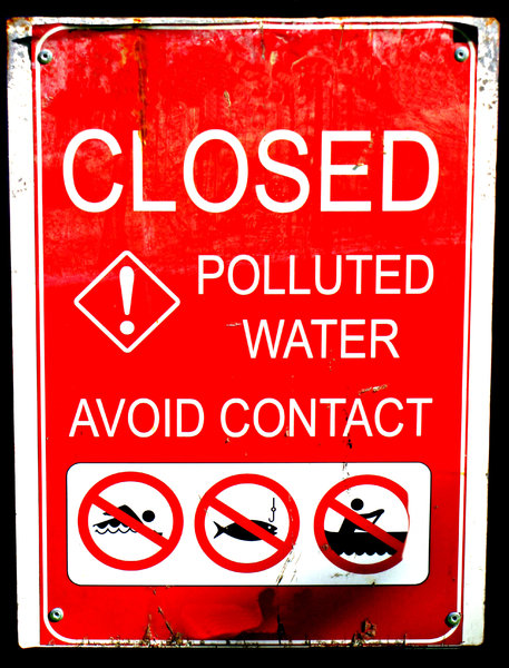 dirty water: worn and weathered red and white sign warning of water pollution and toxicity