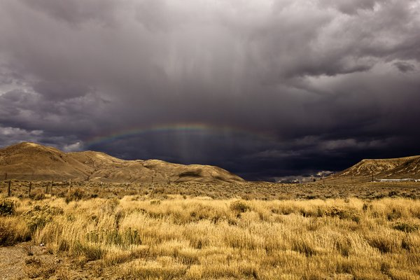 Storm over Mountains: Dark storm clouds with rainbow over western range.