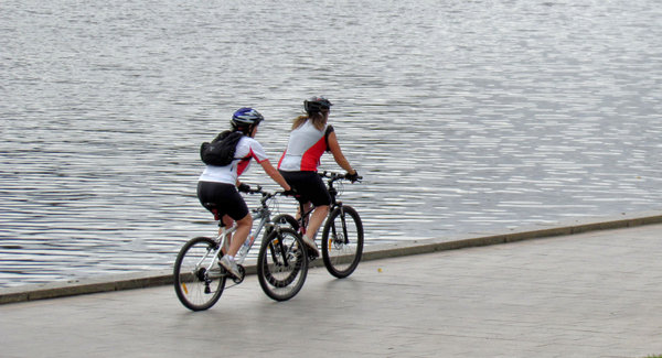 riverside cycling1: two women cyclists riding alongside the river